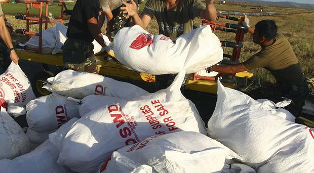 Filipino military personnel unload relief goods to be distributed to those affected by Typhoon Haiyan at the airport in Tacloban (AP)