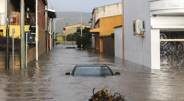 Rescuers reach a flooded street in the Sardinian town of Uras.