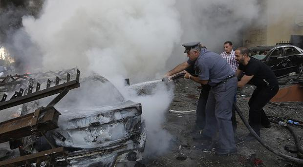 Lebanese police extinguish burned cars at the scene of two explosions which have struck near the Iranian Embassy in Beirut (AP)