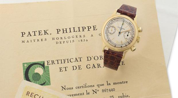 The watch believed to have been worn by the neurosurgeon who signed John F Kennedy's death certificate and an original certificate from the watchmaker (AP/Christie's)