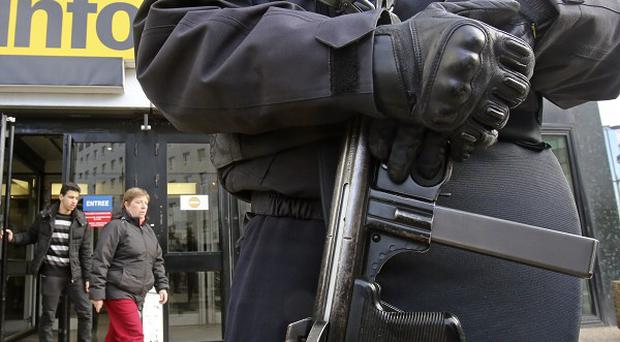A French police officer wearing a bullet-proof jacket stands at the entrance of France Info radio station in Paris (AP)
