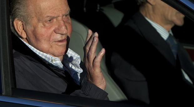 Spain's King Juan Carlos waves from inside a car as he arrives at the private Quiron hospital in Madrid (AP)