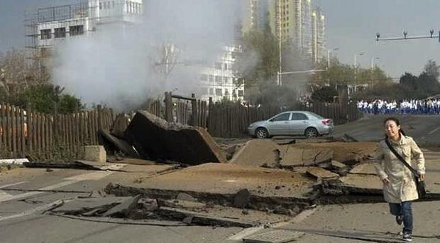 A woman runs in a damaged street following a pipeline explosion in Qingdao in east China's Shandong province (AP)