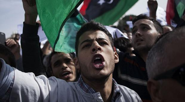 A man shouts slogans against Tripoli-based militias during a protest in Libya's capital city (AP)