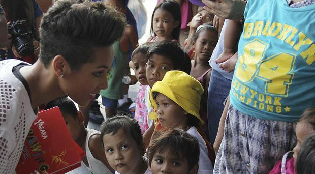 Grammy-winning singer Alicia Keys smiles at a typhoon survivor as she visits Villamor air base in suburban Pasay, south of Manila (AP/Philippine Air Force)