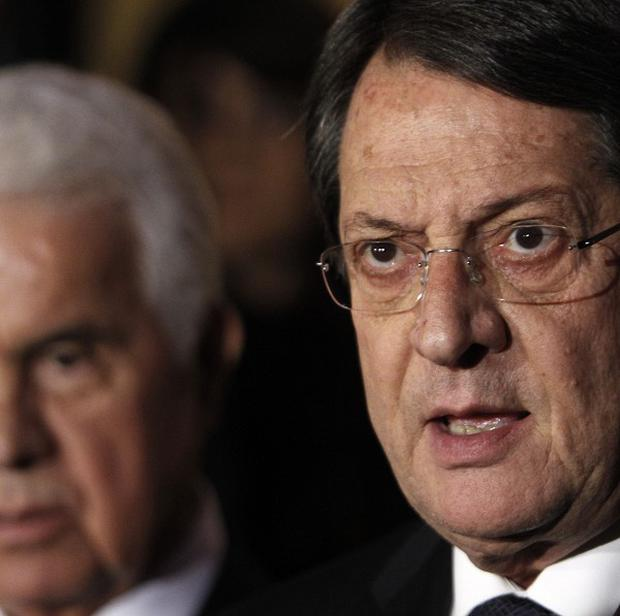 Cyprus' president Nicos Anastasiades, right, and Turkish Cypriot leader Dervis Eroglu, behind (AP)