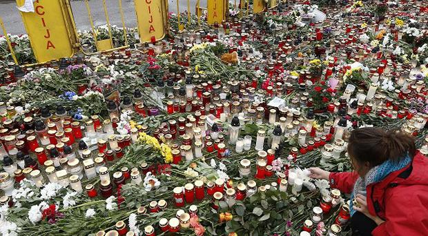 Flowers and candles in front of the Latvian supermarket where 54 people died (AP)