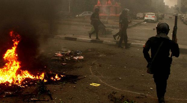 Egyptian riot police move to disperse a protest against a new law regulating demonstrations in Cairo (AP)