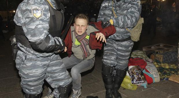Ukrainian riot police officers detain an activist during a rally demanding the resignation of President Viktor Yanukovych in Kiev (AP)