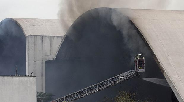 Firefighters watch from a cherry picker as water is sprayed into the Simon Bolivar Auditorium at the Latin America Memorial in Sao Paulo. ,