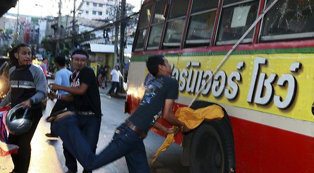 Anti-government protesters attack people they suspect of supporting the current Thai government.(AP Photo/Wason Wanichakorn)