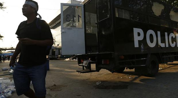 A protester walks next to a destroyed police truck in Bangkok, as the city was braced for more violence (AP)