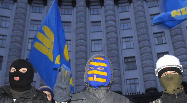 Protesters stand in front of the Cabinet of Ministers' building in Kiev, Ukraine (AP)