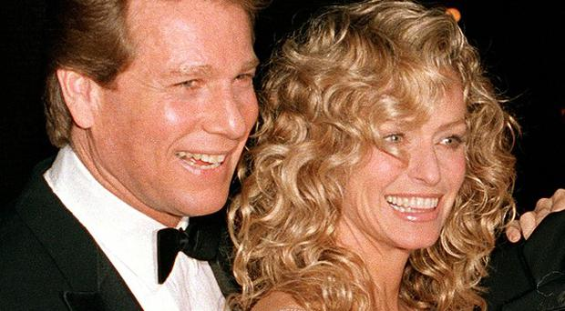 Ryan O'Neal, pictured with Farrah Fawcett at a film premiere in 1989, is locked in a court battle over an Andy Warhol portrait of the actress.