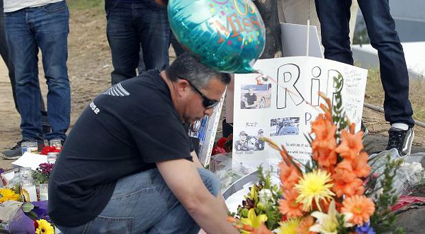 Tributes lie at the site of the car crash that killed actor Paul Walker and another man in Valencia, California. (AP/Nick Ut)