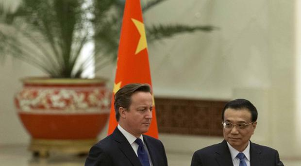 David Cameron is shown the way by Chinese prime minister Li Keqiang during a welcome ceremony at the Great Hall of the People in Beijing.