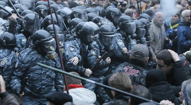 Protesters and riot police clash in front of Ukrainian government offices (AP)
