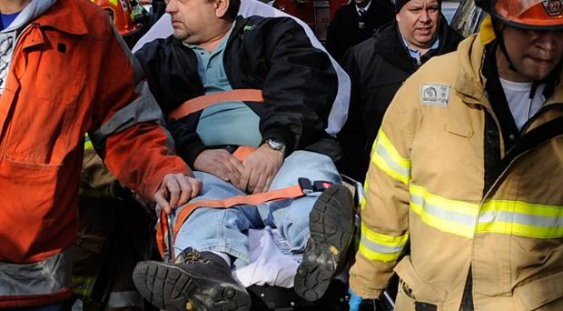 Train driver William Rockefeller is wheeled away from the crash in the Bronx district of New York. (AP/Robert Stolarik)
