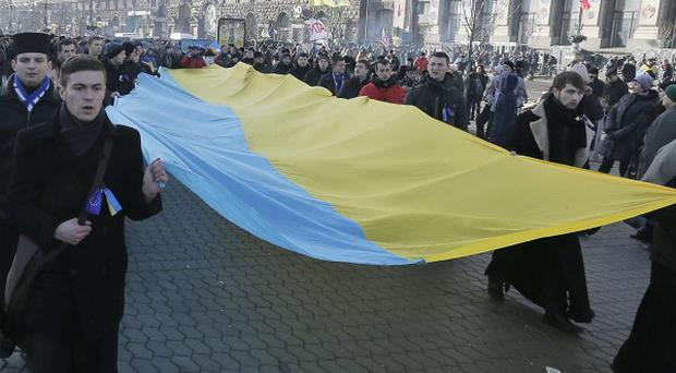 Orthodox priests join the protests carrying a giant Ukrainian flag (AP)