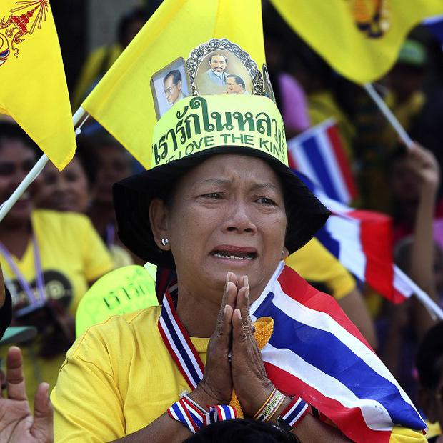 A woman dressed in the royal colour of yellow cries as she watches King Bhumibol Adulyadej's speech on a giant screen. (AP/Manish Swarup)