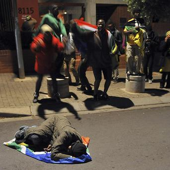 Sowetans mourn the death of former president Nelson Mandela outside his former home. (AP)