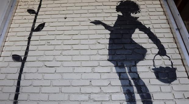 Banksy's Flower Girl stencil has fetched £128,000 at a Beverly Hills auction. (AP /Reed Saxon)