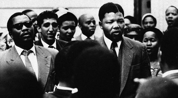 Nelson Mandela, center right, sings with supporters and the accused during the first treason trial outside the Drill Hall in Johannesburg, South Africa, in 1956.