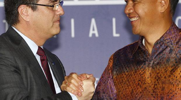 Indonesian trade minister Gita Wiryawan, right, shakes hands with World Trade Organisation director general Roberto Azevedo during the closing ceremony in Bali. (AP/Firdia Lisnawati)