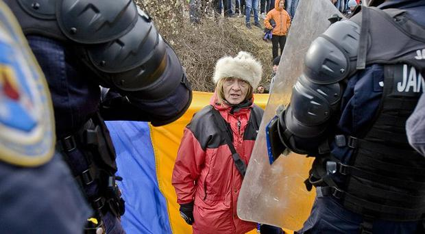 An anti-shale gas exploration protester faces a line of riot police in Pungesti, north-east Romania (AP)