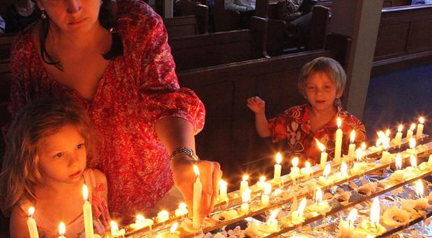 A mother and her children light candles during a church service in honour of Nelson Mandela in Johannesburg. (AP Photo/Tsvangirayi Mukwazhi)