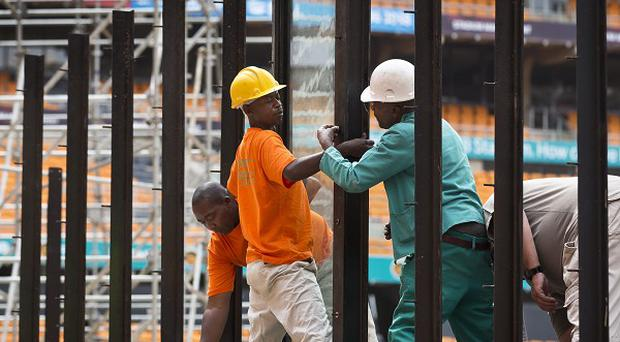 Workers install one of the bulletproof glass panels that will surround VIPs at stadium for the Mandela memorial service (AP)