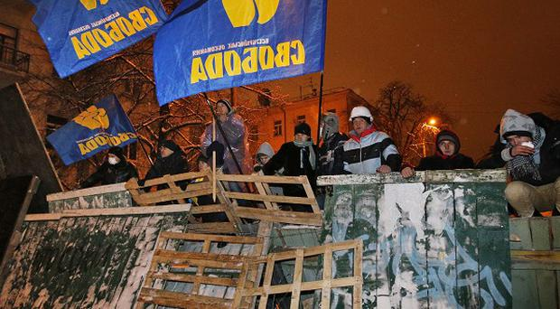 Activists stand on barricades as riot police prepare to storm at the Ukrainian presidential administration building in Kiev (AP)