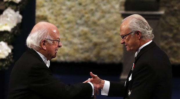 Peter Higgs, left, receives his Nobel Prize for physics from Sweden's King Carl XVI Gustaf