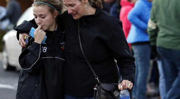 A parent picks up her daughter at a church where students from nearby Arapahoe High School were evacuated to after a shooting on the Centennial, Colorado (AP)