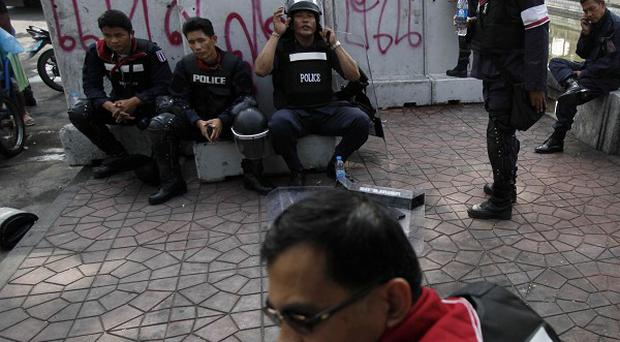 Police officers rest on barriers painted with anti-government graffiti, outside Government House, the prime minister's office compound, in Bangkok (AP)