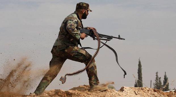 A Shiite fighter clashes with members of the Sunni-dominated Free Syrian Army as more deaths are reported in Aleppo. (AP Photo/Jaber al-Helo, File)