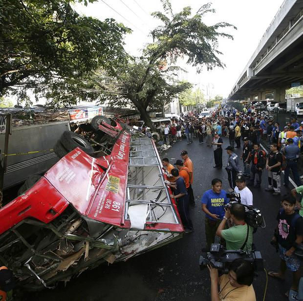 People gather at the scene where a passenger bus plunged from an elevated highway known as the Skyway in suburban Paranaque, southeast of Manila (AP)