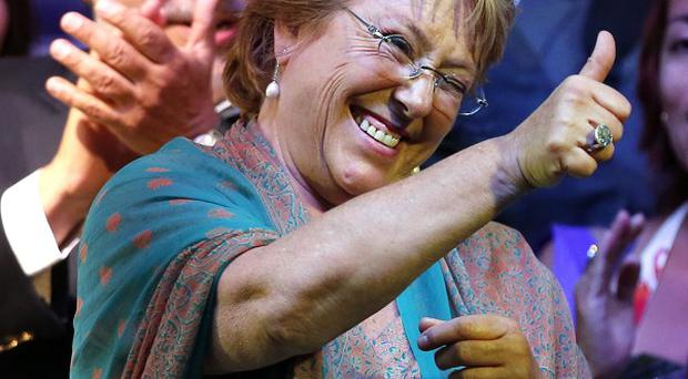 Presidential candidate Michelle Bachelet gives the thumbs up sign during a victory rally in Santiago, Chile (AP)