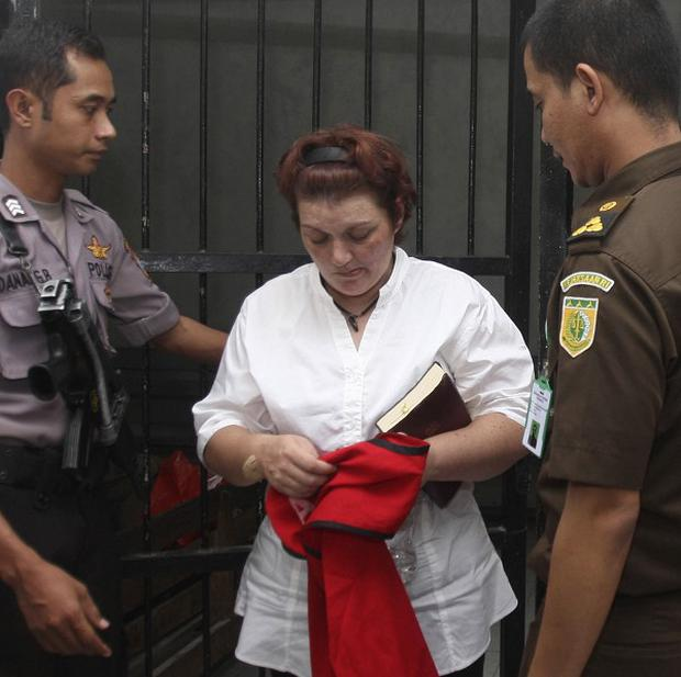 British woman Andrea Ruth Waldeck is escorted out of a holding cell by police after her trial hearing in Surabaya, East Java, Indonesia (AP)