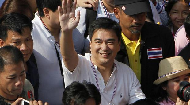 Democrat leader and former prime minister Abhisit Vejjajiva waves as he marches with anti-government protesters in Bangkok (AP)