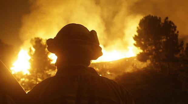 A firefighter looks on as wildfire burns in Northern California (AP/LM Otero)