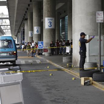 Police investigators examine the scene at Ninoy Aquino International Airport following the shooting of southern Philippine town mayor Ukol Talumpa and his wife (AP)