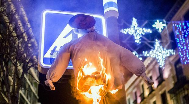 A doll representing Spain's justice minister Alberto Ruiz-Gallardon is set on fire during a demonstration against tougher abortion laws. (AP)