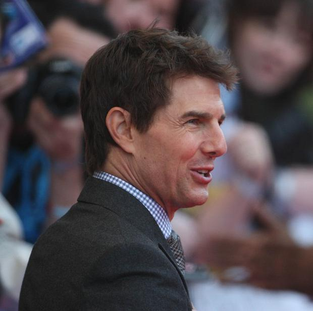 Tom Cruise has settled with a publisher over stories that implied he had abandoned his daughter Suri after his divorce from Katie Holmes.