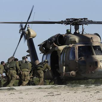 Israeli soldiers carry the civilian shot near the Israel and Gaza border to a helicopter (AP)