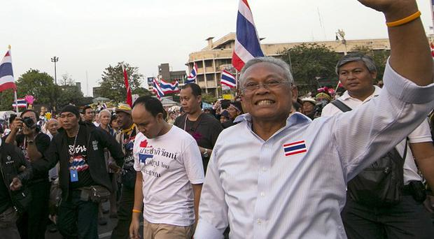 Anti-government protest leader Suthep Thaugsuban, right, waves to supporters in Bangkok. There has been more violence in the Thai capital between demonstrators and police.
