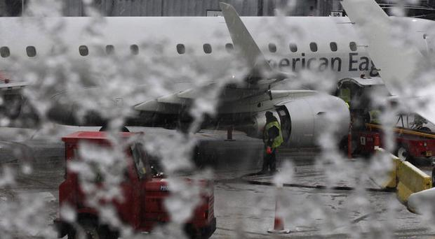 Window on an American Eagle plane is covered with snow before it is de-iced in Chicago following last weekend's ice storm that has been linked with 27 deaths.