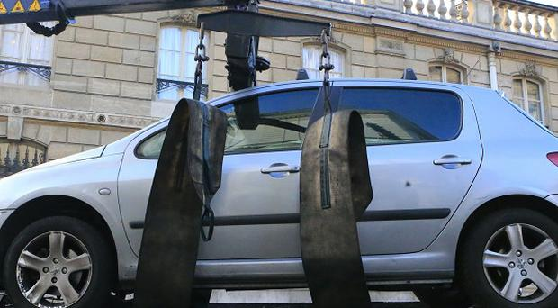 A car is towed away after an unidentified driver tried to ram through a gate of the presidential Elysee Palace (AP)