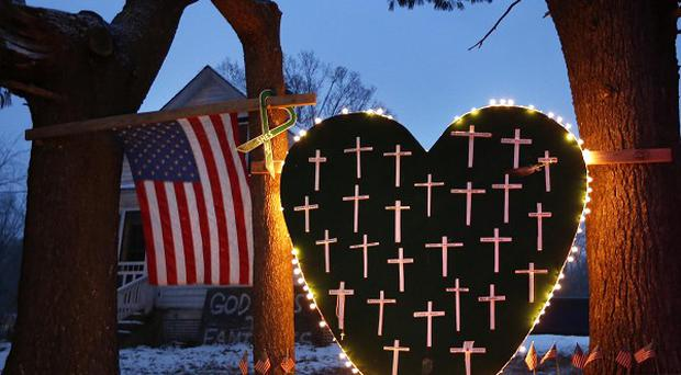 A makeshift memorial with crosses for the victims of the Sandy Hook massacre stands outside a home in Newtown a year after the shootings (AP)