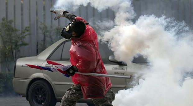 A Thai anti-government protester throws back tear gas canister at riot policemen during a clash at a sport stadium in Bangkok, Thailand (AP)